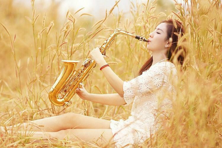 品美女美女在荒草丛里吹萨克斯