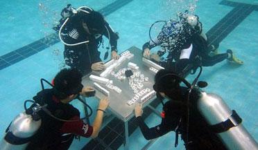 潜水员背着氧气瓶水下打麻将