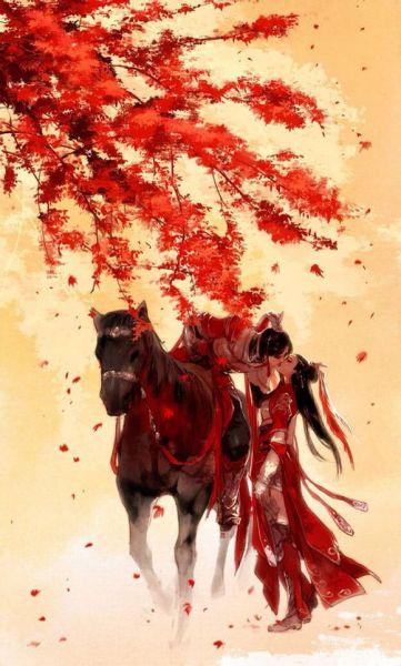 红色枫叶树下,一个骑在马上的红衣图片